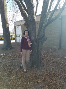 lady standing in front of tree with bus in the background