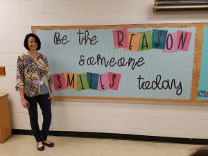 lady standing next to bulletin board that says be the reason someone smiles today