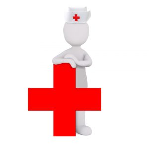 Nurse standing behind a red cross