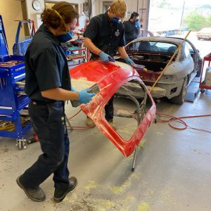 Auto body student works on car