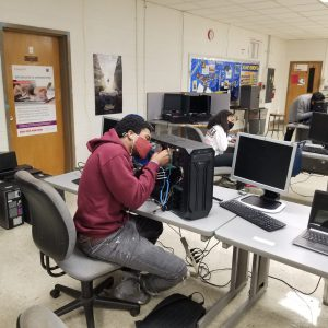 Cybersecurity student working on a computer
