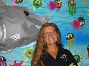 Jamie Walski Teacher of the Year standing in front of shark bulletin board