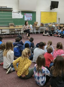 Local news reporter reads to students during Reading Month.