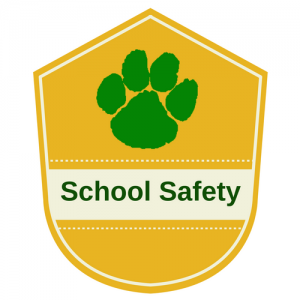 "A gold shield, with a green paw print, stating ""School Safety"" on the shield"