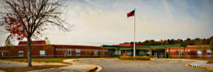 Exterior photograph of Grassfield Elementary School front of school displaying roundabout and school flag pole with the American Flag raised