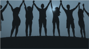 image of people holding rasied hands backlit by the syn