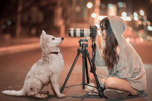 girl with camera taking picture of a dog