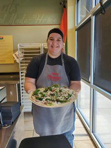 Papa Murphy's employee smiling, holding pizza