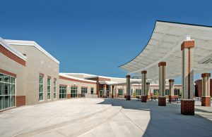 Large breezeway area outside of school on a sunny day with a clear blue sky