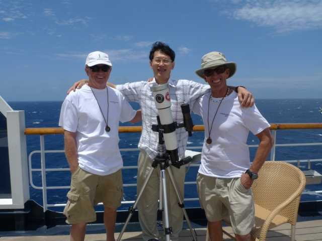 Dr. Hitt and two other passengers aboard Australian ship, behind telescope, prepared to witness eclipse