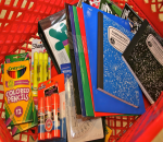 Grocery cart with color pencils, glue sticks, a protractor, highlighters, folders, a binder, and notebooks