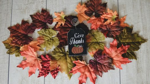 Give thanks sign surrounded by fall leaves