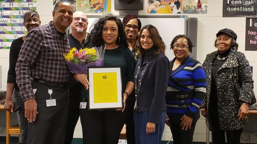 Krystal Miranda (center), Mr. Moyer, principal (left), Mrs. Gould, assistant principal (right), family surrounding