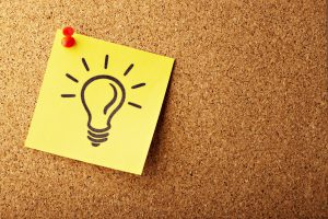 light bulb on yellow post-it note, pinned to bulletin board