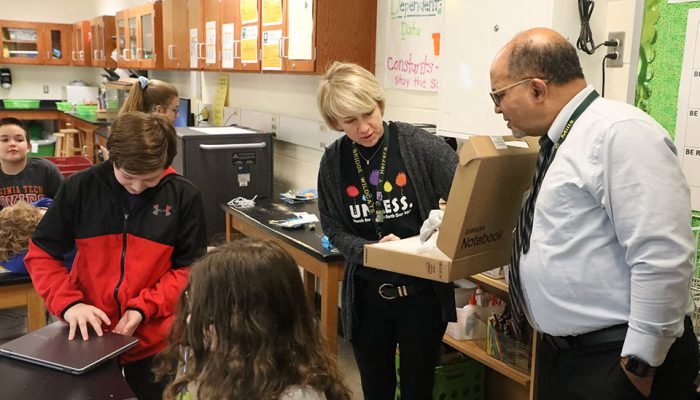 Teacher, Admin, and students at GBMS unbox new computers