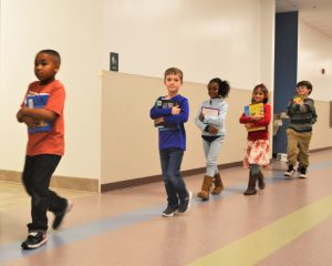 Kindergartners walking single file back to class from the school library.