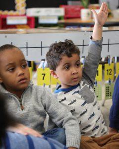 Kindergartner raising hand in classroom.