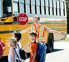 school bus crossing guard helping 3 students cross safely