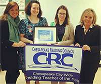 Debra Moyer holding up banner - Chesapeake City Wide Reading Teacher of the Year