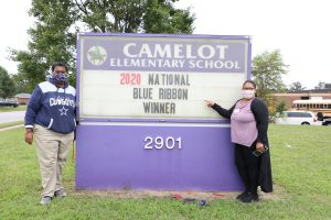 Camelot Staff members stand next to their School Marquee. Marquee reads: CAMELOT ELEMENTARY SCHOOL: 2020 National Blue Ribbon Winner