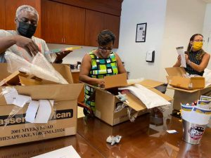 Principals Perry, Ferebee, and Ottley open boxes filled with over $500 of resources to support each school's positive behavior programs.